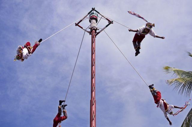 أربعة رجال يبدون راقصين في الهواء، موثوقوين بأربطة إلى سارية مرتفعة للغاية