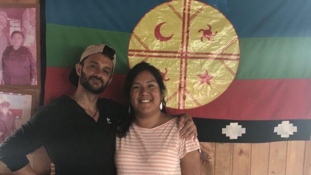 Maria e Daniel em frente a uma bandeira mapuche