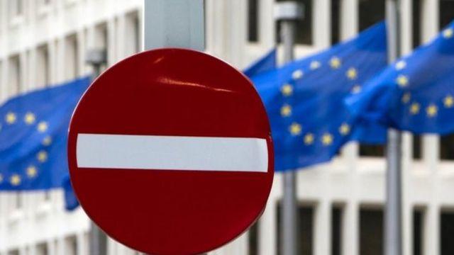 Una señal de stop ante banderas de la Unión Europea