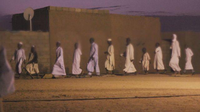 Niños encadenados caminando en fila