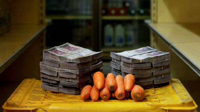 Kilo de zanahorias al lado de billetes de bolívares.
