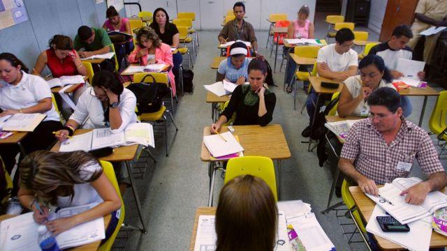 Adultos estudiando en una clase.