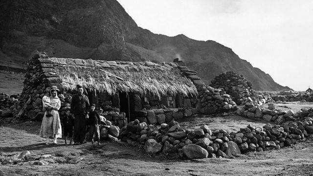 1961ல் எரிமலை வெடிப்புக்கு பிறகு, ஒரு குடும்பம் அங்கு தங்களது வீட்டிற்கு வெளியே நிற்கிறது
