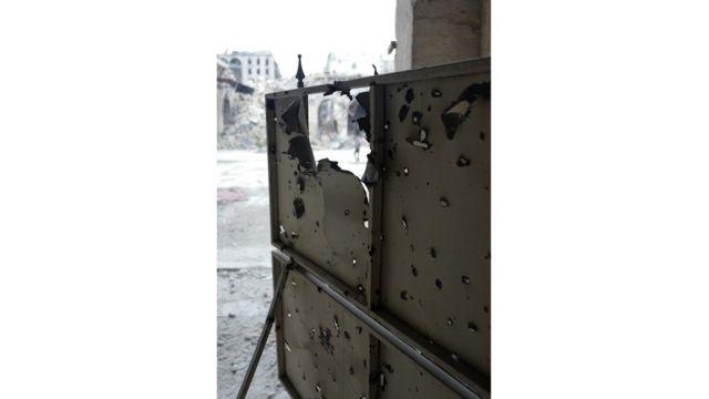 Una entrada lateral improvisada a la mezquita muestra los orificios de balas