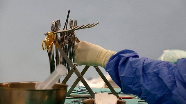 A doctor reaching for surgical equipment