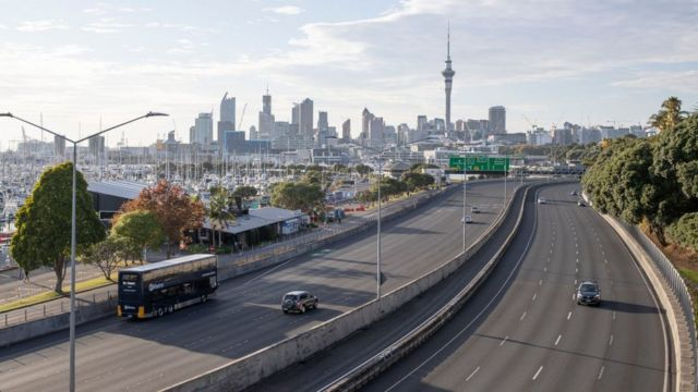 Grande avenida de Auckland quase vazia durante o dia, com prédios vistos ao fundo