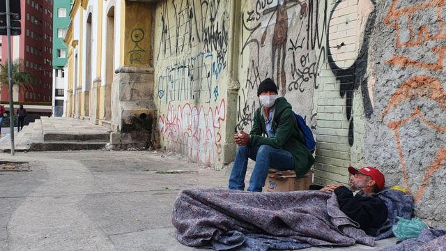 Osvaldo Pereira e o amigo Claudinei França Cruz na calçada onde dormem no centro de São Paulo