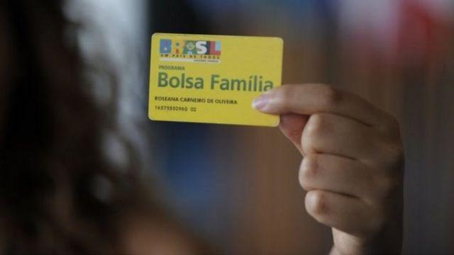 Mulher segura cartão do Bolsa-Família
