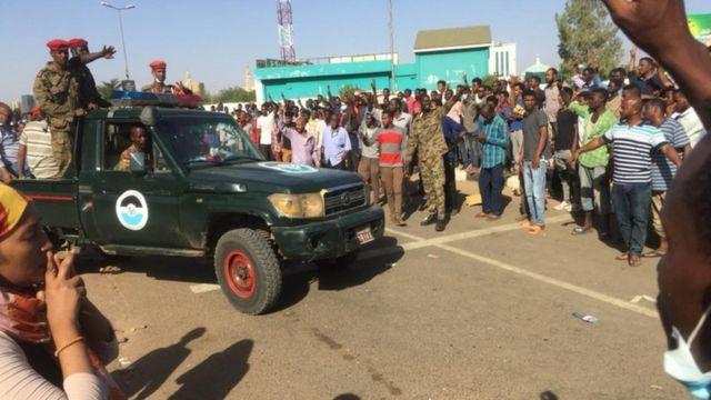مركبة للجيش تمر بين المعتصمين قرب مقر قيادة الجيش في الخرطوم