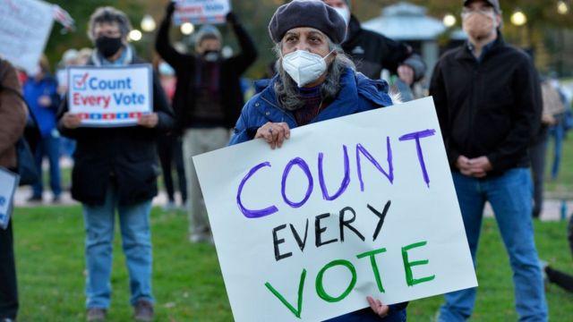 Una mujer manifiesta para exigir que se cuenten todos los votos.