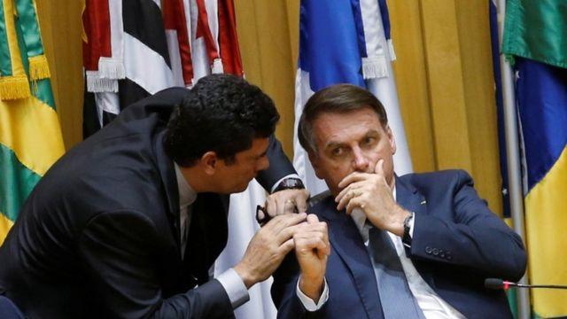 Em pé, Moro se curva para ouvir Jair Bolsonaro, que fala com a mão na frente da boca, como se estivesse cochichando; ambos estão dentro de uma sala com várias bandeiras ao fundo
