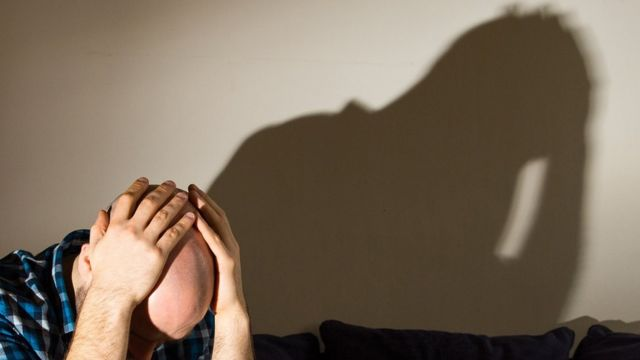 Model posing as depressed man with head in his hands, shadow of his image on wall