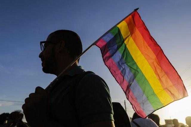 Hombre sosteniendo una bandera de arcoiris