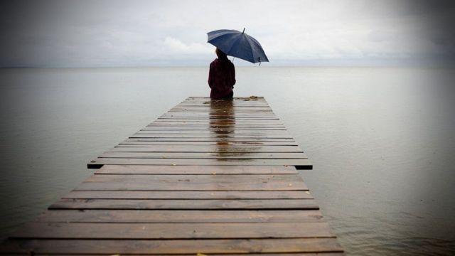 Homem sentado em passarela sobre a água