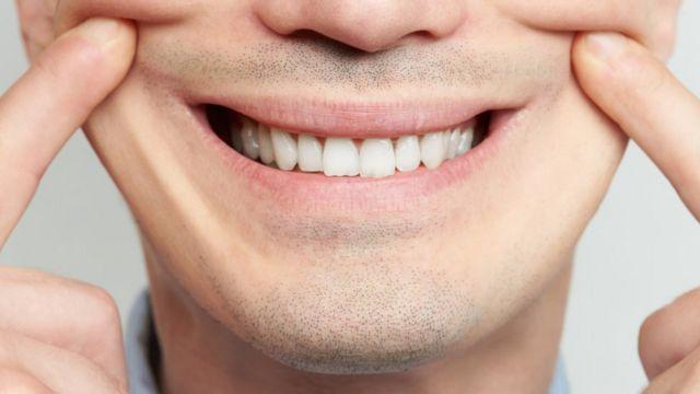 Homem sorrindo de forma forçada