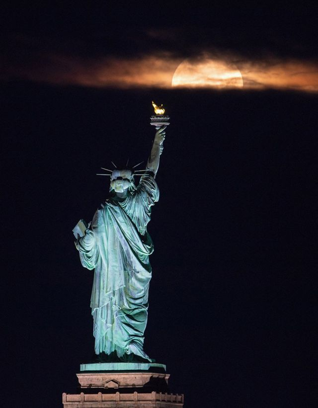 The Statue of Liberty in New York seemingly looks towards the rising moon