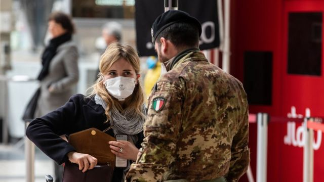 An Italian soldier speaks to a passenger at Milano Centrale train station on March 10, 2020 in Milan, Italy