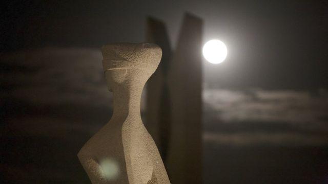 Estátua representando a Justiça em brasília, com Lua cheia ao fundo