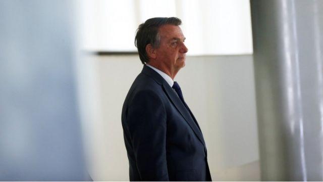 Bolsonaro em pé em corredor, com sorriso contido