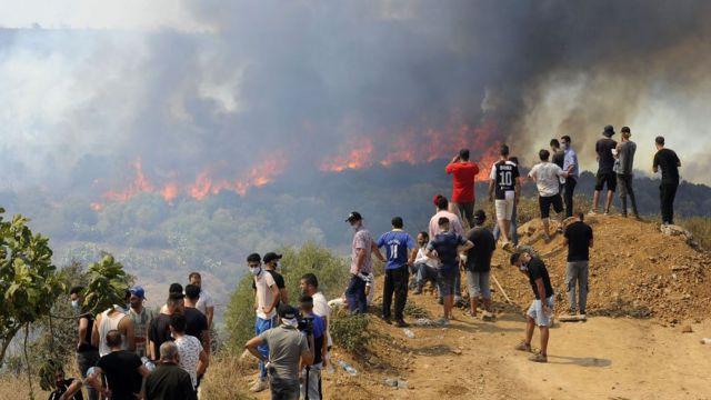 Personas ven cómo avanza el incendio en Argelia.