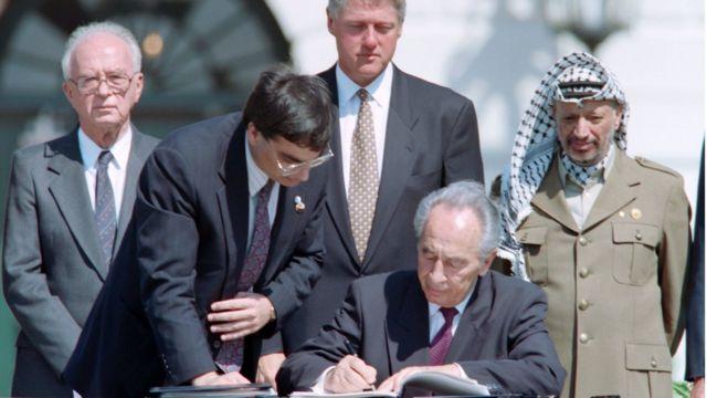 अमरीकी राष्ट्रपति कार्यालय ह्वाइट हाउस में इसराइली प्रधानमंत्री यित्ज़ाक राबिन, अमरीकी राष्ट्रपित बिल क्लिंटन, पीएलओ प्रमुख यासिर अराफ़ात की मौजूदगी में 1993 में ऑस्लो समझौते पर दस्तख़त करते इसराइली प्रधानमंत्री शिमोन पेरेज़.