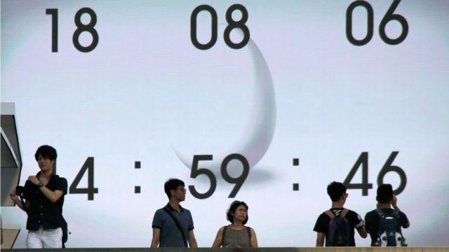 Pessoas passam em frente a relógio digital em rua do Japão