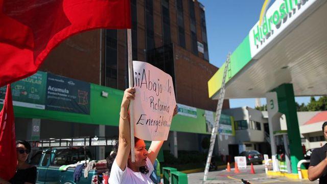 Una mujer sostiene un cartel contra la reforma energética.