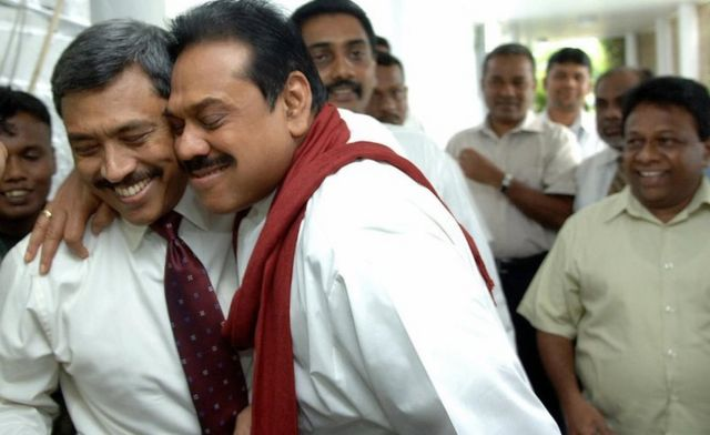 Colombo, SRI LANKA: Sri Lankan Defence Ministry Secretary Gotabaya Rajapakse (L) is hugged by elder brother Sri Lankan President Mahinda Rajapakse (C) in Colombo, 01 December 2006, after narrowly escaping assassination in a suicide bomb attack in the Sri Lankan capital. A suspected Tamil suicide bomber attacked a defence ministry convoy carrying the president's brother, killing at least one soldier, police said. Gotabaye Rajapakse, secretary to the defence ministry and brother of President Mahinda Rajapakse, was unhurt after the blast in the heart of the Sri Lankan capital.
