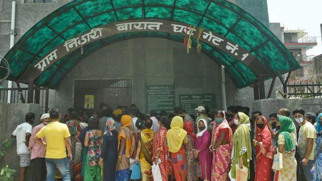 Orang-orang mengantre di sebuah pusat vaksinasi di India