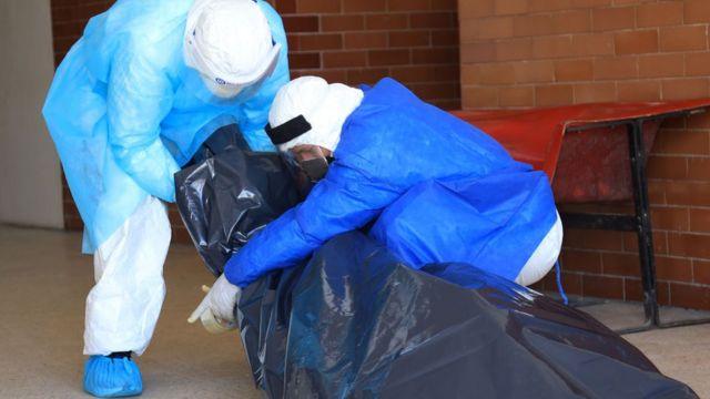 Personal sanitario con un cadáver en una bolsa.