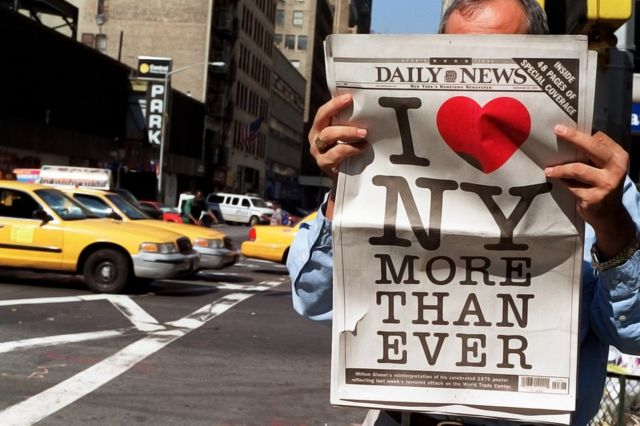 A man reads a copy of the New York Daily News newspaper bearing a poster designed by Malcolm Glaser (19 September 2001)