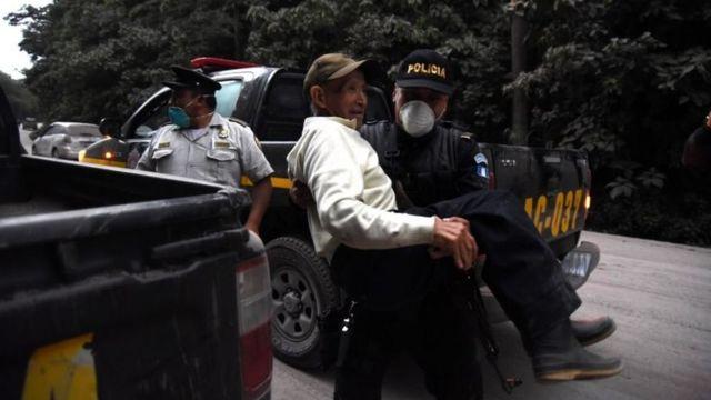 Un policía carga a un anciano