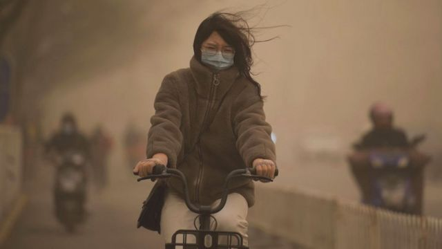 Mulher pedalando com máscara, olhos fechados e com céu turvo ao redor dela