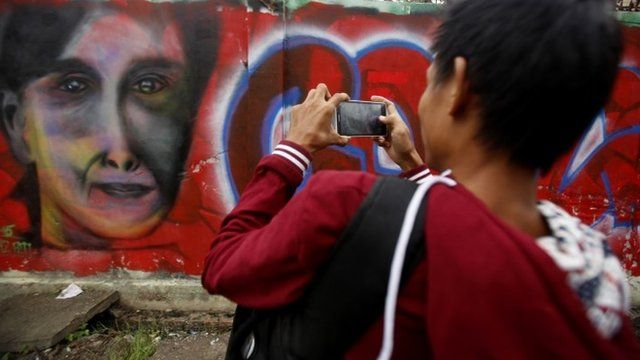 Young man takes picture of mural