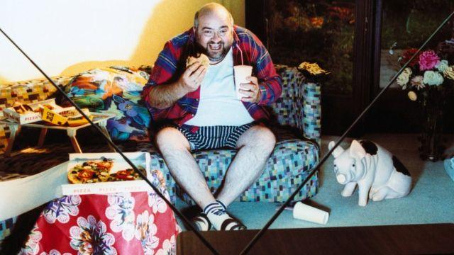 Hombre sentado en el sofá mirando la TV