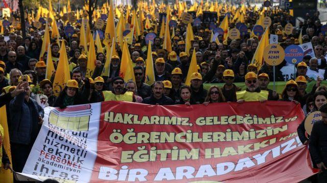 """Dezenas de professores e pesquisadores da Turquia são vistos em rua de Ancara, com capacetes e bandeiras amarelas, além de com cartaz dizendo: """"Estamos juntos pelo direito de nossos estudantes à educação"""""""