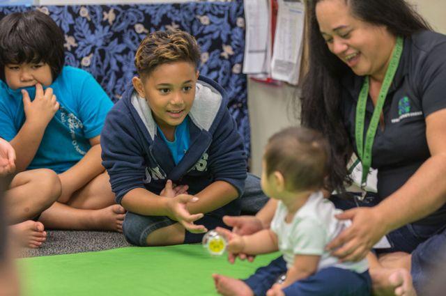 Niños interactúan con un bebé durante el programa.