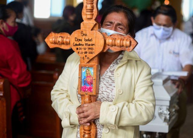 Señora lleva una cruz con el nombre de la mujer fallecida: Dora Isabel.