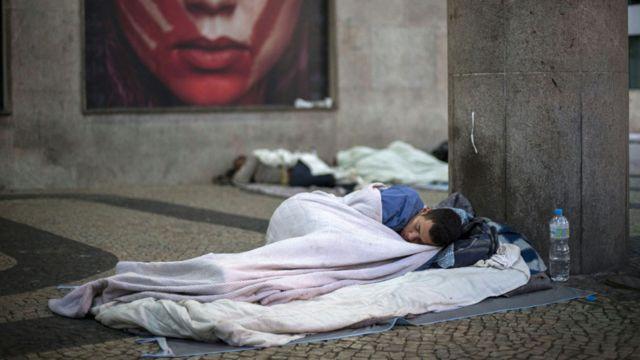 Hombre duerme en la calle en Brasil.