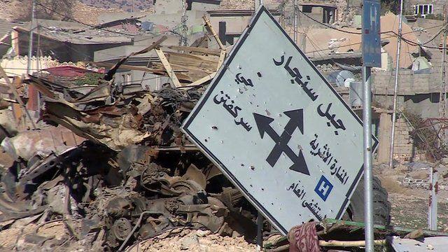 Road sign lies amongst rubble