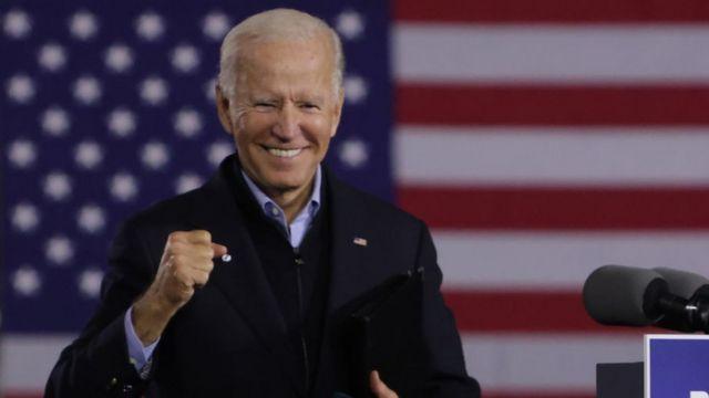 Biden faz gesto de vitória em frente a bandeira dos EUA projetada ao fundo