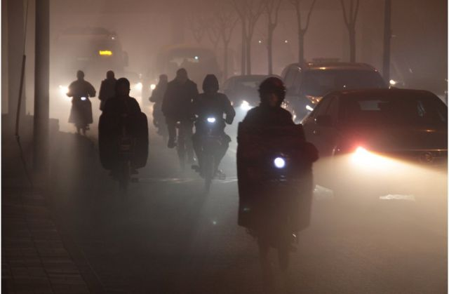 Cyclists ride along a road in heavy smog on 23 December 2015 in Beijing, China