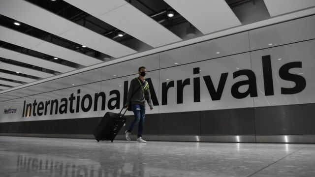 A man wearing a mask arrives at Heathrow
