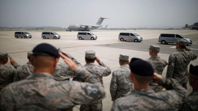 遺骨を乗せた車両に敬礼する米空軍兵士ら