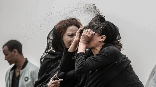 Familiar de una víctima del accidente de avión de Ethiopian Airlines arrojándose tierra a la cara.