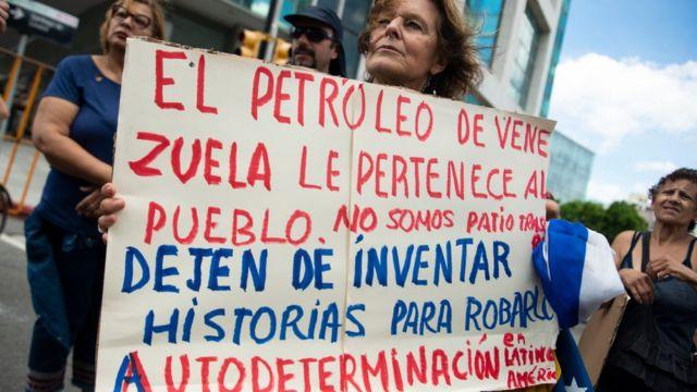 """Mujer protestando con letrero que dice: """"El petróleo de Venezuela le pertenece al pueblo"""""""