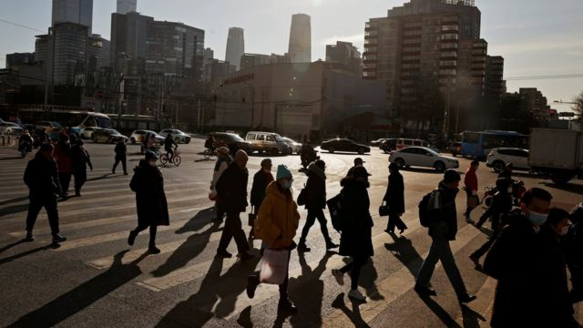 People cross a street during morning rush hour in front of the skyline of the central business district (CBD) in Beijing, China December 15, 2020.