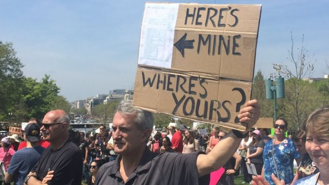 一名示威者公開展示他的稅務紀錄,並舉著一個牌子,問特朗普的紀錄在哪。