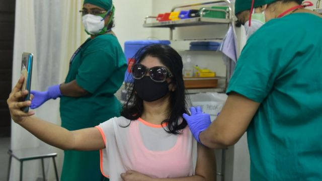 A woman taking a selfie while getting vaccinated