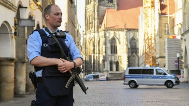 A policeman stands guard in Muenster after Saturday's van attack